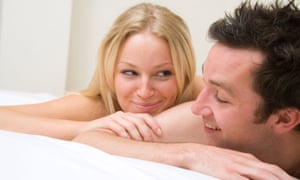 Young naked couple cuddling and happy in bed