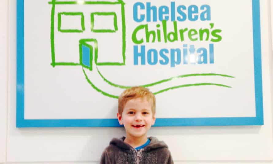 Child smiling in front of hospital sign