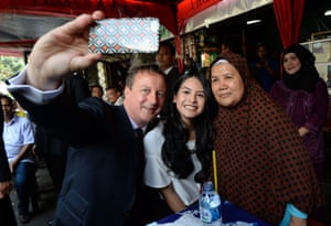 David Cameron takes a selfie as he is shown around a street market by actress and singer Maudy Ayunda (centre). He ate banana fritters with stall holder Ibu Djuna (right) on his second day in Indonesia as part of a four-day visit to south-east Asia