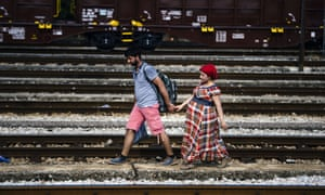 <strong>Gevgelija, Macedonia</strong> A Syrian migrant and his pregnant wife walk on train tracks on the Macedonian-Greek border, trying to catch a train to Serbia and the north European countries. The situation forced migrants, fleeing conflict-torn and impoverished countries across Africa, the Middle East and Asia, to either walk or more recently cycle for some 200km (124 miles) through Macedonia to get to the border with Serbia