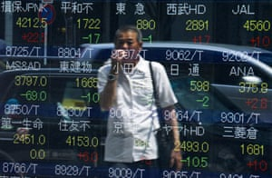 <strong>Tokyo, Japan </strong>A man looks at stock prices displayed at a board showing market indices. Japan's Nikkei share average dropped to a more than two-week low as investors worried that a fresh rout in Chinese shares would damage China's economy and as commodity prices tumbled