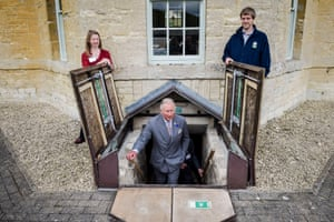 People hold open trapdoors for the Prince of Wales as he ascends the steep stairs up from the cellar during his visit to the Old Prison