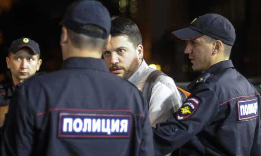 Leonid Volkov (centre) is escorted by police officers at the Novosibirsk election commission building.