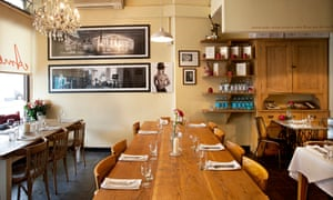 A long rectangular table, pictures on the walls, a chandelier at Amoul's