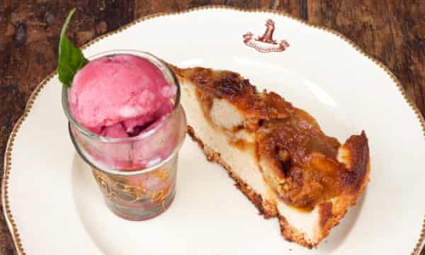 The pomegranate sorbet in a tall glass next to a slice of caramelised apple cake