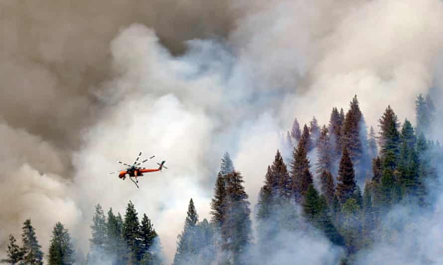 A helicopter flies over Willow Creek Canyon on Monday, where a wildfire that has burned more than 1500 acres is still just 5% contained.