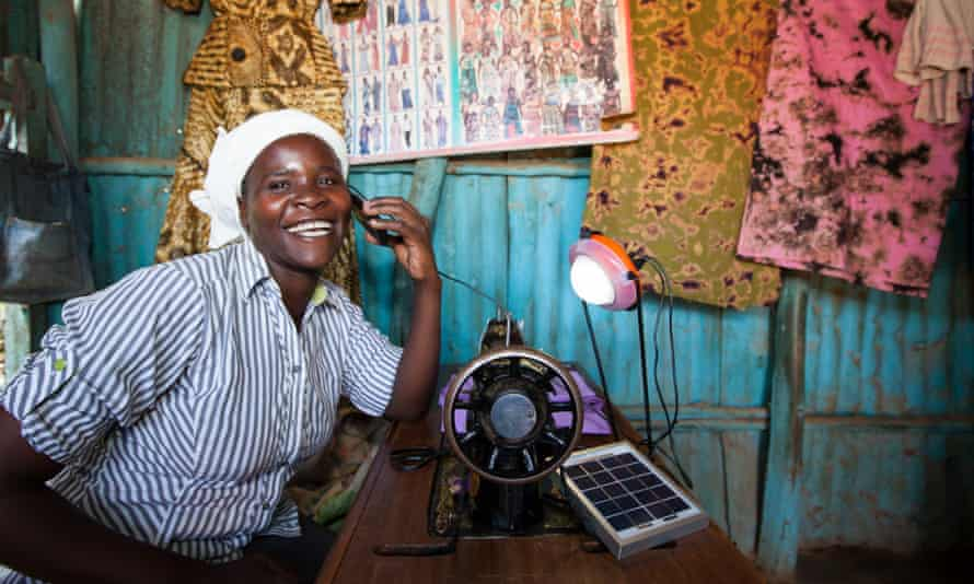 Rose Owino a tailor in Migori, Kenya uses a solar light to charge her phone