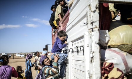 Kurdish refugees get on a bus in Turkey having fled the civil war in Syria.