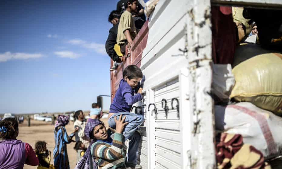 Kurdish refugees get on a bus in Turkey having fled the civil war in Syria.