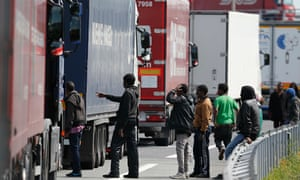 Migrants gather near a line of lorries in Calais