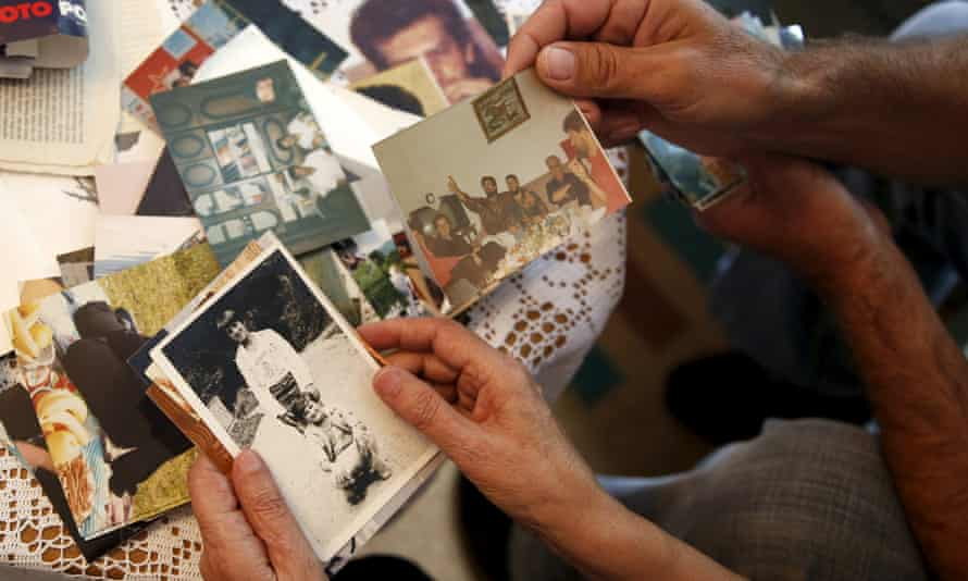 Hajra Catic and Edmin Jakubovic look at pictures of Hajra's son at her home in Srebrenica.