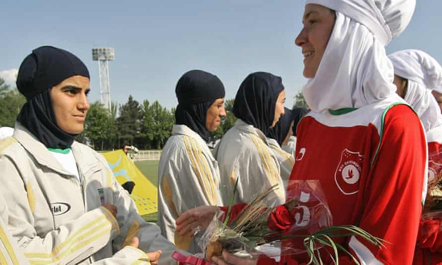 Players from Iran's women national football team exchange flowers with players from Germany's Al-Dersimspor team before a friendly match at Tehran's Ararat stadium 28 April 2006. Women football fans are prevented from attending games in the Islamic Republic.