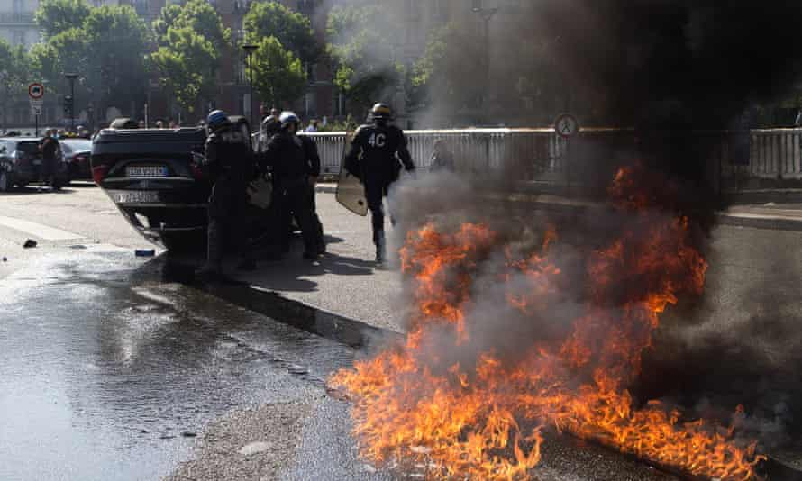 Riot police officers stand by an overthrown car during a taxi drivers demonstration in Paris.
