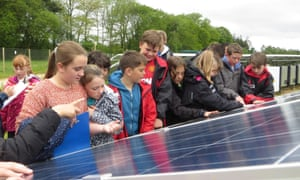 Children inspect panels at a UK solar farm. Solar power is supply 16% of UK electricity on Friday, the industry says.