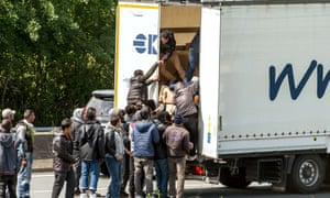 Migrants climb in the back of a lorry on a road leading to the Channel tunnel at Calais.