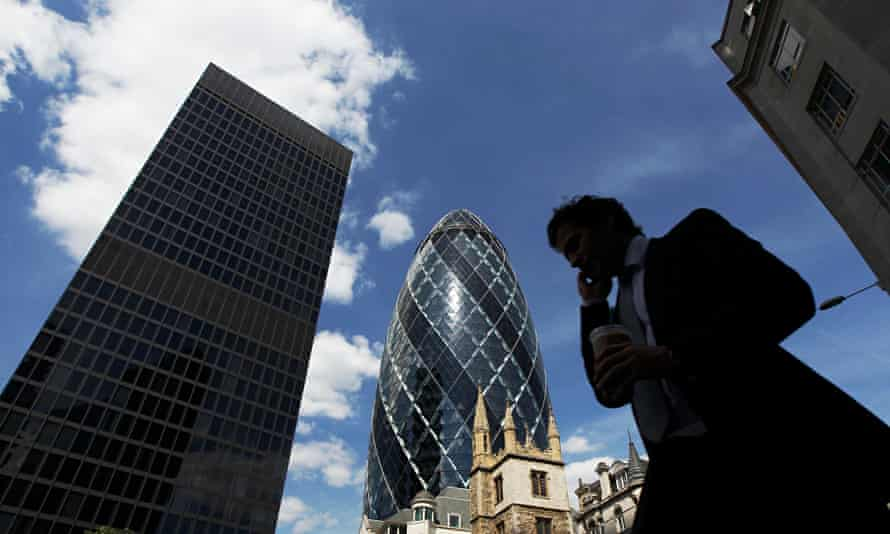A man passes the Swiss RE building, also known as the Gherkin, in London.