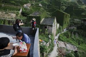 Tourists visit the abandoned fishing village of Houtouwan