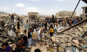 People gather at a market destroyed in air strikes carried out by the Saudi-led coalition in Sana'a, Yemen, on 20 July.