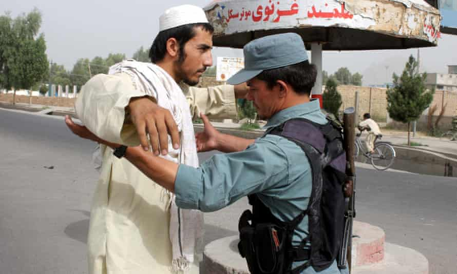 Afghan official frisks a man in Kandahar after security was intensified following reports of Omar's death.