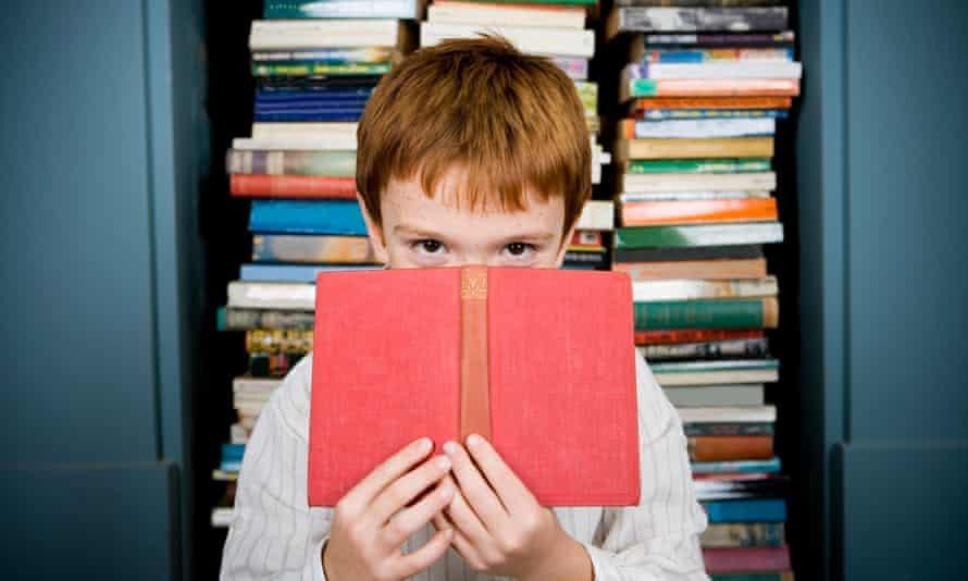 Boy peering over top of book