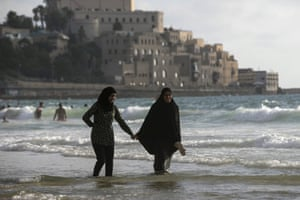 Muslim women walk along beach in Tel Aviv.