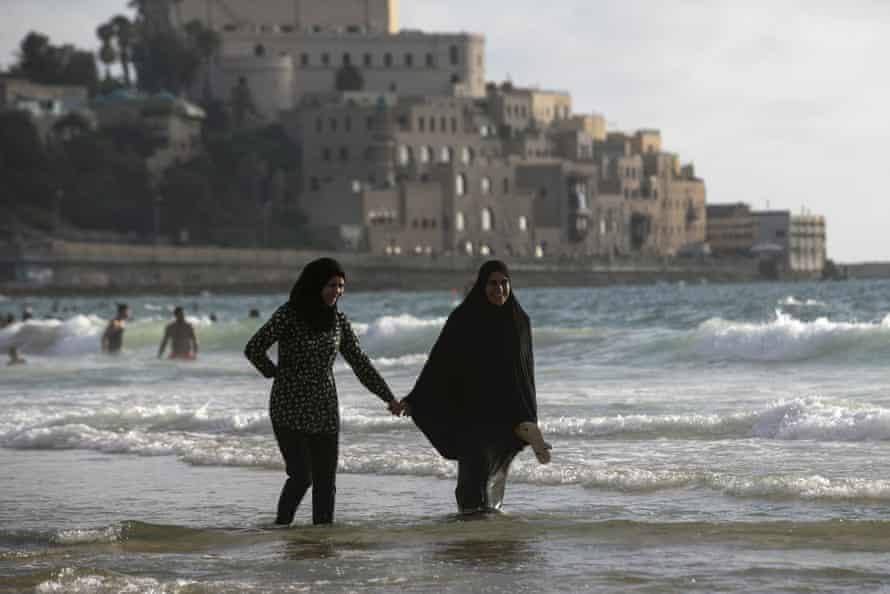 Muslim women walk along beach in Tel Aviv.