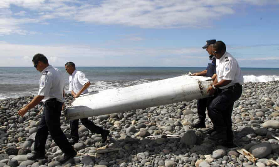 Officers carrying pieces of aircraft debris washed ashore on Réunion.