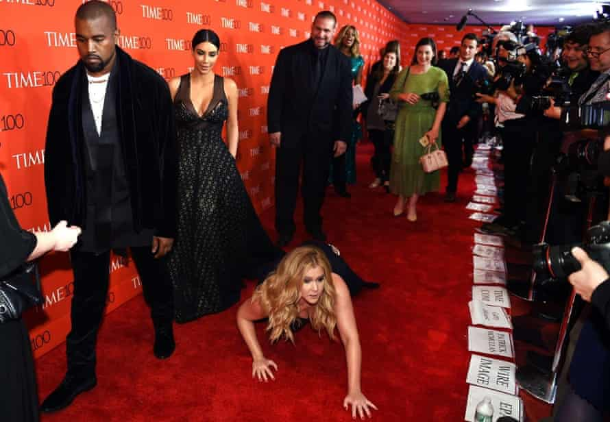Schumer pretends to trip and fall on the floor in front of Kim Kardashian and Kanye West at the Time 100 Gala in New York.