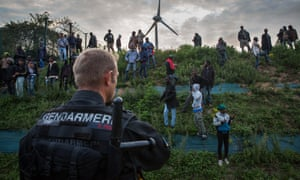 A French police officer faces migrants outside the Eurotunnel terminal
