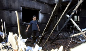 A Palestinian boy inspects a house that was badly damaged in the attack.