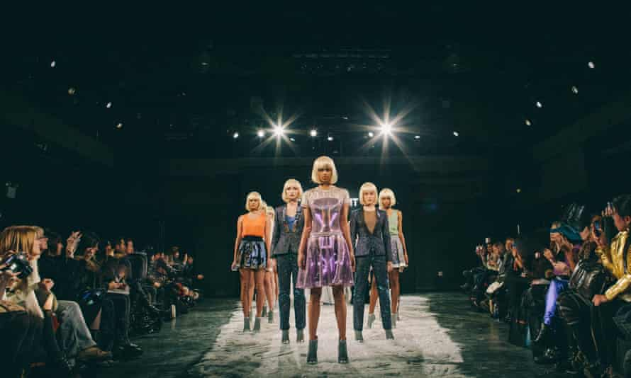 Models on a fashion catwalk wearing smart textile clothing lit by LEDs