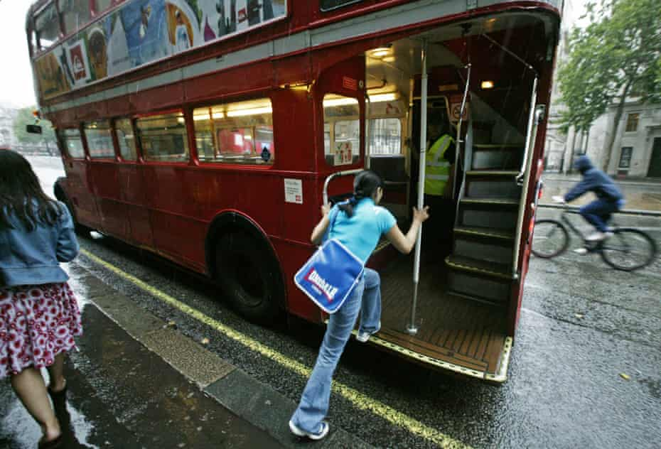 A passenger 'hopping on' a old-style Routemaster bus.
