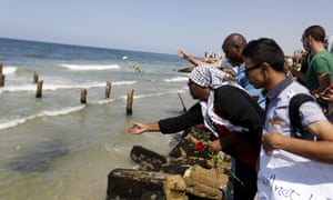 Palestinians mourning the loss of compatriots who boarded a boat to Europe that was intentionally capsized by traffickers last September cast roses in to the Mediterranean sea.