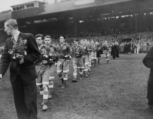 13 November 1945: With the second world war just ended, Dynamo Moscow toured Britain. Here, the Russian players walk out onto the pitch at Stamford Bridge, carrying bouquets for their Chelsea opponents. The match was so popular that ticket touts were able to charge up to £5 for tickets that had a face-value of just ten shillings and the official attendance of 74,496 is considered at least 25,000 short of the true attendance.