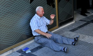 Giorgos Chatzifotiadis, sitting on the ground crying outside a national bank branch in Thessaloniki.