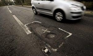 Car driving past a large pothole