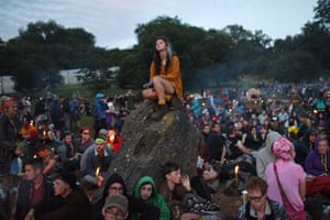 Revellers wait for the sunrise in the Stone Circle area as Glastonbury festival drew to a close on Sunday 28th June.