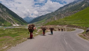 Women carry baskets filled with firewood collected from the mountains towards their homes in Kashmir, India.