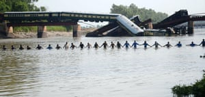 Army soldiers hold hands while conducting a search operation after a train fell into a canal near Gujranwala in Pakistan