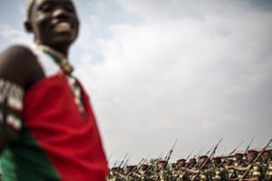 A traditional Burundian drummer looks on while soldiers march in formation towards the Prince Rwagasore stadium in Bujumbura on the country's 53rd independence anniversary