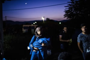 A migrant woman and her baby leave a train on the Tabanovce border crossing between Macedonia and Serbia on her way north to Europe