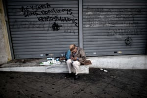 An elderly man sells tissues outside a shuttered shop in central Athens.