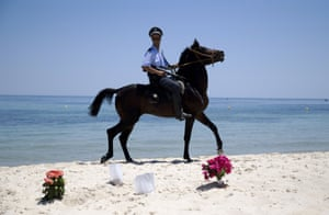 A Tunisian policeman patrols the beach in front of the Riu Imperial Marhaba hotel in Sousse following the beach shooting two days earlier