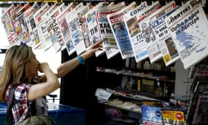 """The newspaper on the right showing a map of Greece reads """"The country stands up on Monday""""."""
