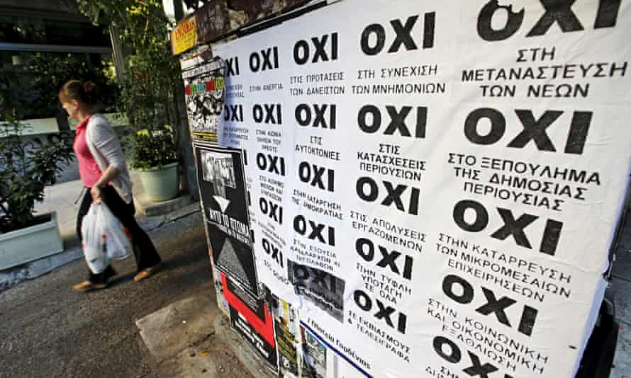 """A woman in Athens walks past referendum campaign posters reading """"No"""" in Greek."""