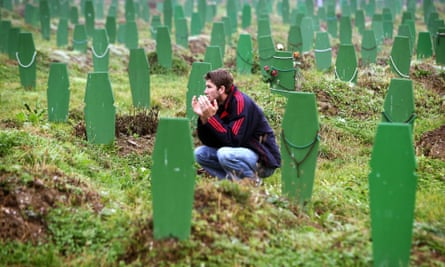 A Bosnian Muslim man prays between graves of victims of the 1995 Srebrenica massacre after the morning prayers on the first day of Eid al-Fitr November 3, 2005.