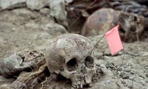 Bosnian forensic experts uncover and catalogue bodily remains found in a mass grave in the eastern village of Kamenica, near the town of Zvornik, close to the border with Serbia on 25 July 2002.