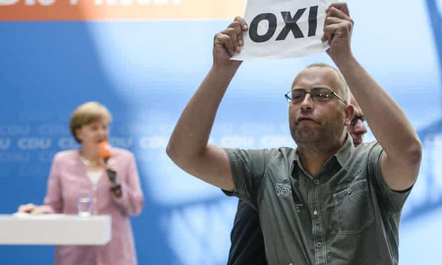A protester interrupts Angela Merkel as she addresses and audience of her Christian Democratic Union party members on Saturday.