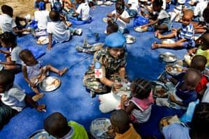 A UN soldier in Haiti distributes food to children in Port-au-Prince.