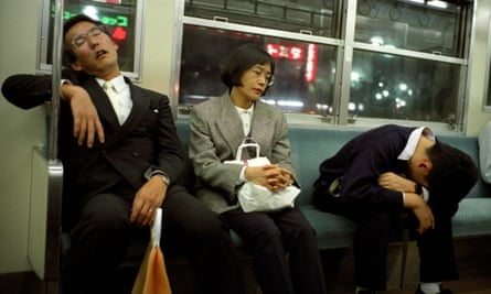 People sleeping on a commuter train in Tokyo, where 'inemuri' (being present while sleeping) is common practice.